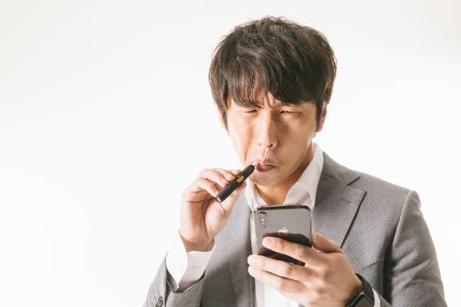 スマホ片手にiQOSを吸う男性